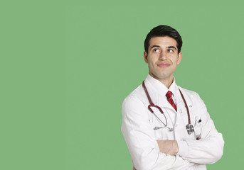 Male doctor in lab coat standing with arms crossed looking up over green background