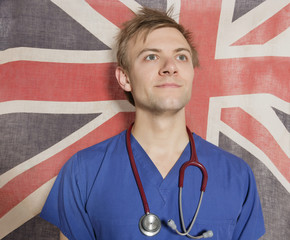 Confident male surgeon looking up with British Flag in background