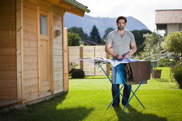 Mann macht Hausarbeit Wäsche aufhängen im Garten
