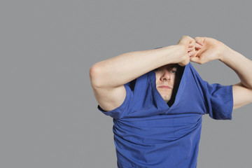Young man removing t-shirt over colored background