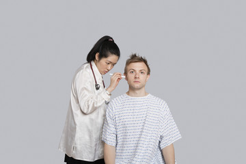 Doctor examining patient's ear with flashlight