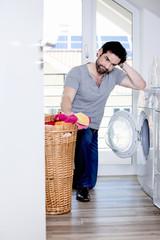 Mann ist verzweifelt bei so viel Wäsche für die Waschmaschine
