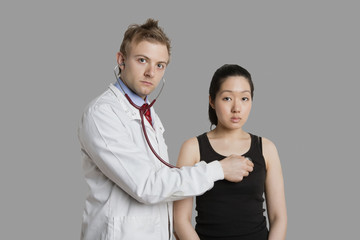 Doctor examining female patient with stethoscope