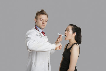 Doctor checking temperature of female patient