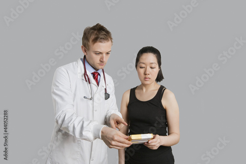 Male doctor suggesting medication to female patient