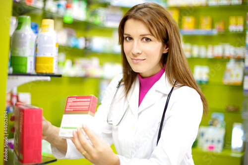 Smiling female doctor in pharmacy with medicine
