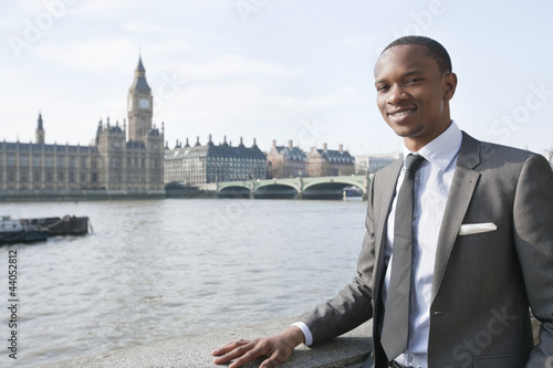 Portrait of a smiling African American businessman with buildings in background