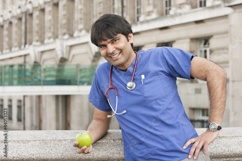 Portrait of an Indian male doctor holding a green apple