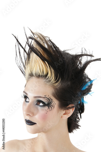 Close-up of gothic woman with face painting and spiked hair over white background