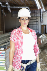 Portrait of beautiful young woman architect wearing hardhat at construction site