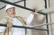 Portrait of mature man climbing scaffold