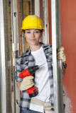 Portrait of beautiful mid adult contractor with drill