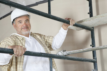 Portrait of mature man climbing scaffold
