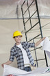 Happy mid adult worker holding building plans while looking away