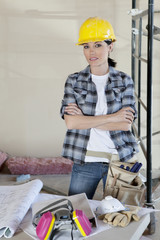 Portrait of female worker standing with arms crossed at construction site