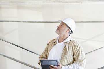 Mature male architect making a note in digital tablet while looking up at construction site
