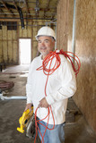 Portrait of a smiling male construction worker holding a power saw and a red electric wire