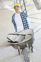 Male construction worker standing with a wheelbarrow