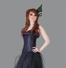 Redheaded teenage girl posing over gray background