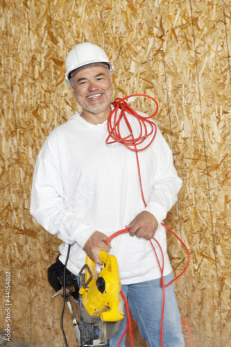 Portrait of a happy male construction worker holding a power saw and a red electric wire