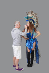 Mature makeup artist grooming fashion model during photo shoot over gray background