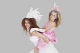 Portrait of beautiful young bride giving piggyback ride to bridesmaid over gray background