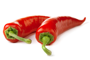 Two red chili peppers isolated on a white background