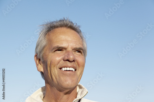 Portrait of a happy mature man over blue sky