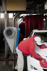 Employee wiping vehicle after washing in car wash