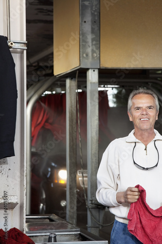 Half-length portrait of happy car wash owner
