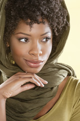 Beautiful African American woman looking away over colored background