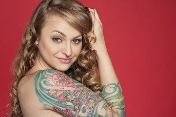 Portrait of beautiful young tattooed woman over colored background