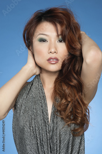 Portrait of beautiful young Chinese woman posing over colored background