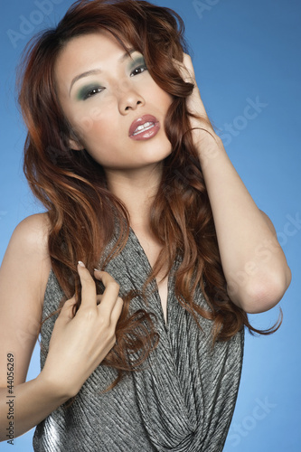 Beautiful Chinese woman with sensual pose over colored background