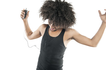 Young man with curly hair enjoying while listening to mp3 player over white background