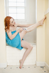 Young woman shaving her legs on the side of the bathtub