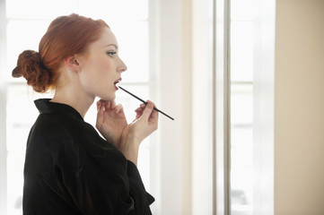 Profile view of a young woman in robe applying lip liner