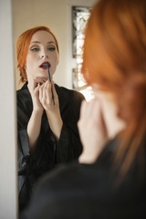 Young female applying lip liner in front of mirror