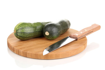 Fresh zucchini on chopping board isolated on white