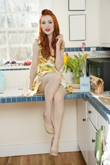 Portrait of a beautiful young woman in a dress at kitchen counter