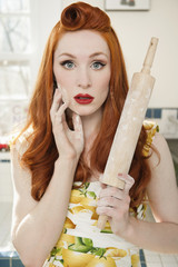 Portrait of a shocked redheaded woman with a rolling pin