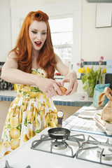 Young redheaded woman preparing omelet in kitchen