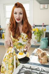 Portrait of a young redheaded woman cooking omelet