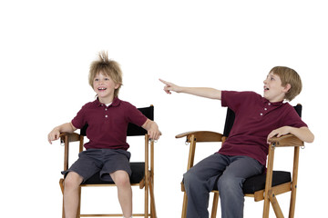 Pre-teen boy pointing at friend's hair while sitting on director's chair over white background