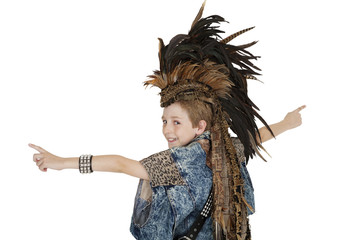 Portrait of boy in costume with headdress looking back over white background