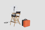 Director's chair and reflector umbrella with suitcase in studio