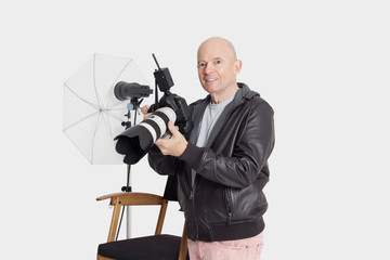 Portrait of happy senior man with camera standing in photographer's studio