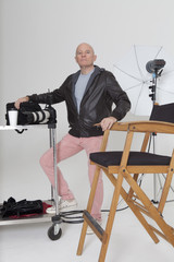 Full length portrait of senior photographer with equipments in studio
