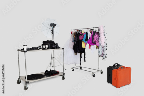 Clothes rack and reflector umbrella with suitcase in studio
