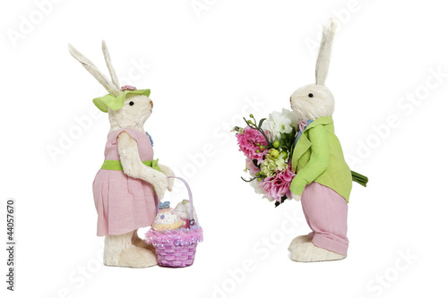 Stuffed toys portrayed as male with flowers and female with basket over white background